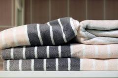 Serviettes, pantoufles de tapis et peignoirs pliés sur une étagère d'un cabinet dans un hôtel image stock