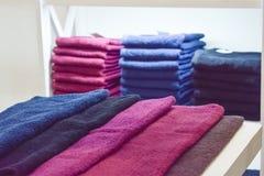 Serviettes pelucheuses roses, marron, pourpres, noires pour la beauté et le salon de STATION THERMALE Pile des serviettes dans un image libre de droits