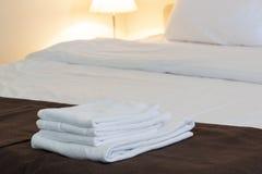 Serviettes pliées blanches, literies de toile sur le lit rangé photos stock
