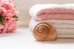 Serviettes pliées sur le compteur de salle de bains avec des fleurs image libre de droits