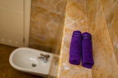 Serviettes pourpres dans la salle de bains en petits pains Photographie stock