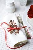 Servilleta blanca adornada con la planta roja de la Navidad de la cinta, SE de la tabla Foto de archivo