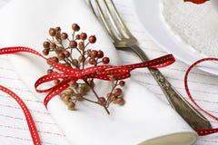 Servilleta blanca adornada con la planta roja de la Navidad de la cinta, SE de la tabla Imágenes de archivo libres de regalías
