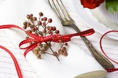 Servilleta blanca adornada con la planta roja de la Navidad de la cinta, SE de la tabla Fotos de archivo