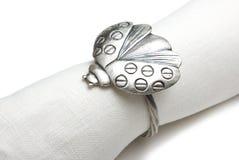 Servilleta con un anillo bajo la forma de ladybug. Fotos de archivo libres de regalías