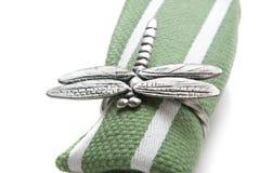 Servilleta con un anillo bajo la forma de libélula. Fotografía de archivo