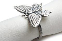 Servilleta con un anillo bajo la forma de mariposa. Fotos de archivo