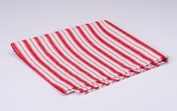 Servilleta doblada blanco rojo en el fondo blanco Fotografía de archivo