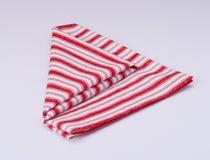 Servilleta doblada blanco rojo en el fondo blanco Imagen de archivo