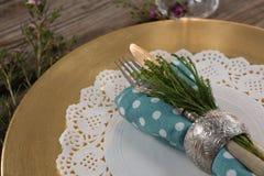 Servilleta doblada con los cubiertos y flora colocada en palcemat Imagenes de archivo