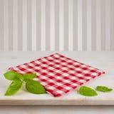 Servilleta y hojas a cuadros rojas en la tabla sobre fondo del vintage Fotos de archivo