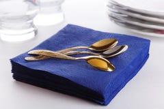 Servilletas de papel con las cucharas, las placas y los vidrios Fotos de archivo