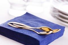 Servilletas de papel con las cucharas, las placas y los vidrios Fotografía de archivo