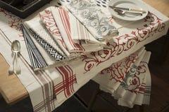 Servilletas y mantel de diversos diseños en la tabla y el taburete imagen de archivo