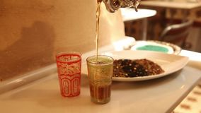 Serving arabic tea in two glasses stock video footage
