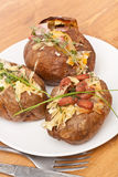 Serving of Baked Jacket Potatoes. Three Baked Jacket Potatoes with beans, cheese and herbs Royalty Free Stock Image