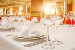Serving banquet table in a restaurant on the sunset. Table setting for dinner or banquet in restaurant on the sunset Stock Image
