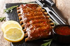 Free Serving BBQ Pork Ribs With Chili Sauce And Lemon Close Up On A Slate Board. Horizontal Stock Photo - 144874600