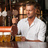 Serving the best beer in town. Handsome bartender in white shirt Royalty Free Stock Images