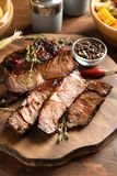 Serving board with delicious barbecued steak and spices. On wooden table stock images