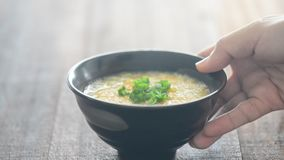 Serving a bowl grain congee. Serving a bowl rice congee on dining table, natural lighting background stock video footage