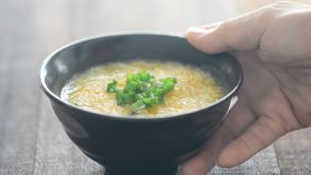 Serving a bowl rice congee. Serving a bowl grain porridge on dining table, natural lighting background stock footage