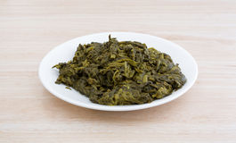 Serving of canned spinach on a white plate Stock Photo