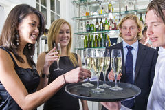 Serving champagne. A waiter serving glasses of champagne on a tray in a restaurant Stock Image
