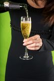 Serving champagne in glass. Detail of woman hand with champagne glass on green background Royalty Free Stock Photography