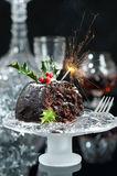 Serving Of Christmas Pudding. Christmas pudding decorated with lit sparkler in Xmas setting Royalty Free Stock Image