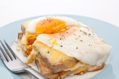 Serving of Croque Madame. Ham, Cheese, Bechamel Sauce and Egg Traditional French Toasted Sandwich cut in half Royalty Free Stock Images