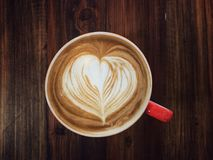 Serving cup of love, love heart latte art coffee. On white and red cup on the vintage wooden table, love in your cup stock images
