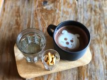 Serving cute dog face Latte art in Black cup and water glass on wooden tray royalty free stock photos