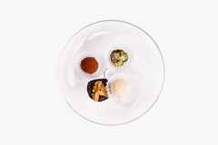 Serving of decorative petit fours and bonbons. Serving of decorative petit fours and fondant bonbons on a white plate viewed from above for a tasty Christmas or Royalty Free Stock Images