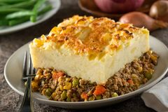 A serving of delicious homemade shepherds pie. A serving of delicious homemade shepherds pie with ground meat, mashed potato, carrots, peas, corn, and cheddar Stock Images