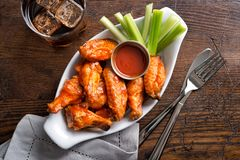 Pub Style Chicken Wings. A serving of delicious spicy buffalo chicken wings on a pub style restaurant table top royalty free stock images