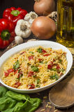 Serving dish with orzo and roasted red peppers. Ready to eat surounded by fresh ingredients stock photo