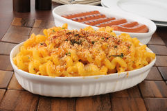 Serving dishes of macaroni and cheese and hot dogs Stock Photos