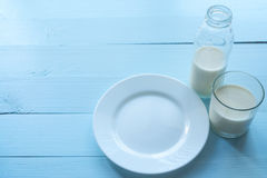 Serving of empty white plate, bottle and glass of milk Royalty Free Stock Photos