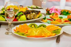 Serving the festive table in the restaurant: stuffed fish, citrus, croutons_ royalty free stock photos