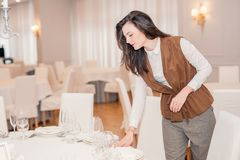 Young woman is serving a festive table in a restaurant royalty free stock photo