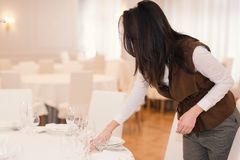 Young woman is serving a festive table in a restaurant stock photography