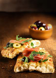 Serving of focaccia bread with ham and rocket Stock Images