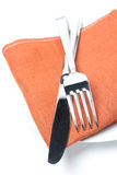 Serving - fork, knife and napkin on a plate, isolated Stock Image