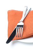 Serving - fork, knife and napkin on a plate, isolated, close-up Royalty Free Stock Photo