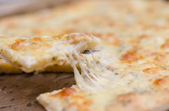 Serving a four cheese pizza with melted cheese Royalty Free Stock Images