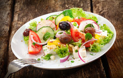 Serving of fresh mixed salad. Serving of fresh healthy mixed salad with leafy greens, radish, tomato, olives and cheese served on a rustic wooden table Royalty Free Stock Image