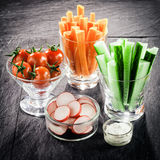 Serving of fresh vegetable crudites on a buffet. With individual glass containers of carrot and cucumber batons, sliced radish and cherry tomato with a Royalty Free Stock Photos