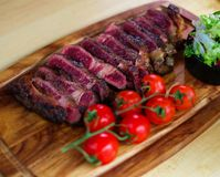 Serving freshly cooked beef steak on a wooden board