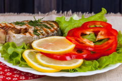 Serving fried grill steak of salmon and salad in plate on table Royalty Free Stock Image
